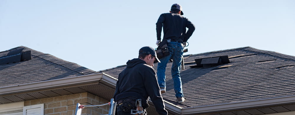 Two roofing contractors inspecting roof